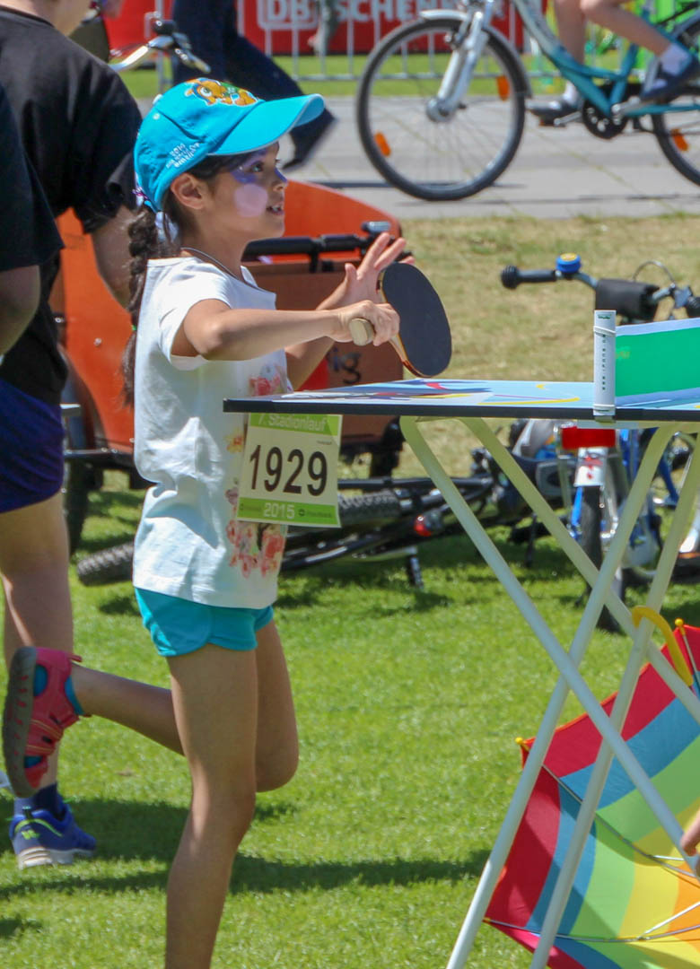 Kleines Mädchen mit Schirmmütze spielt Tischtennis