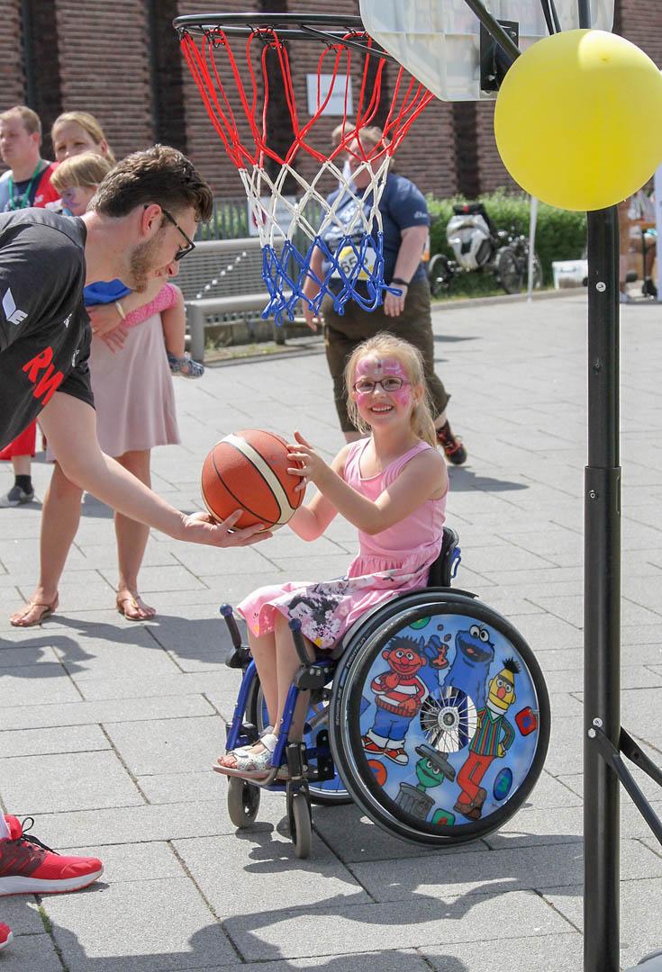 Ein pink geschminktes Mädchen im Rollstuhl bekommt einen Basketball gereicht.