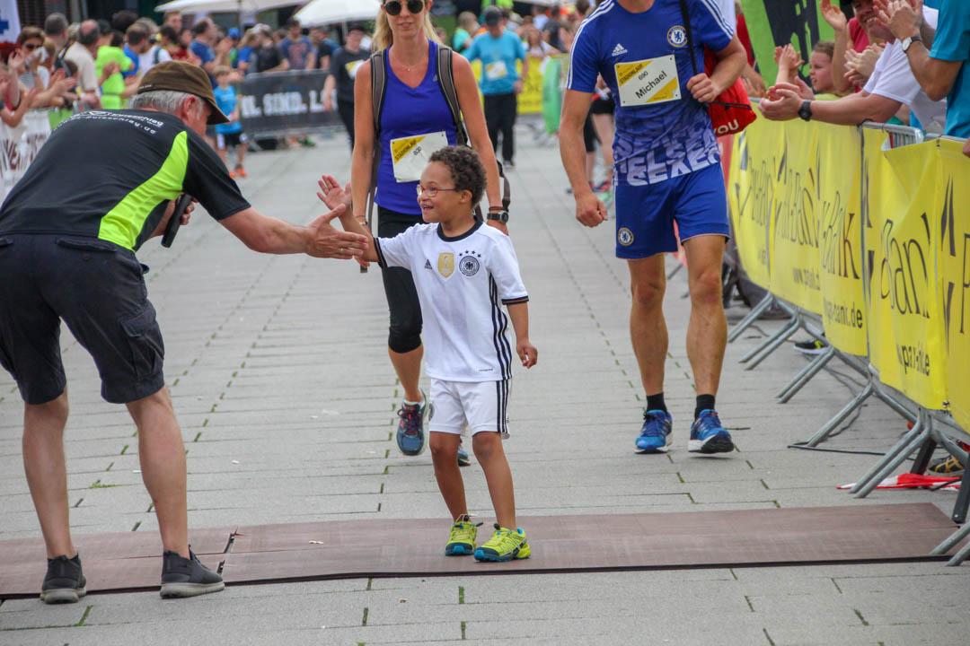 Älterer Läufer gratuliert Kind nach dem Lauf
