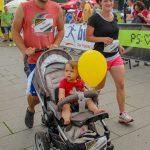 Familien.Spiele.Fest | Eltern mit Kind im Kinderwagen. Das Kind hält einen Luftballon. Inklusion in allen Bereichen.