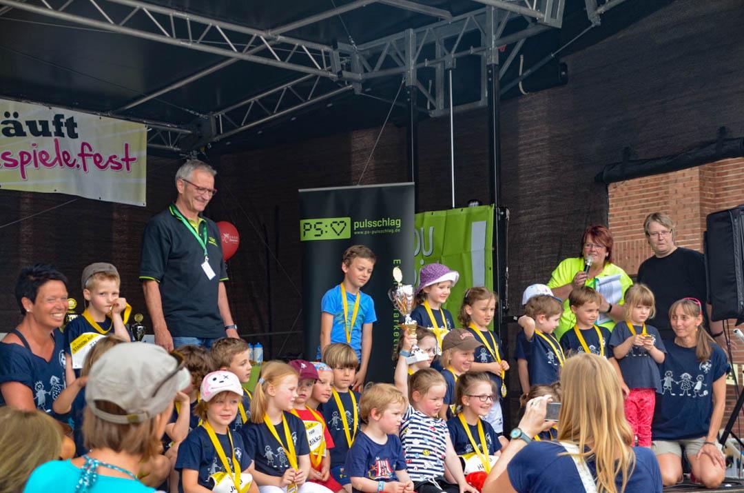 Auf der Bühne sind ganz viele Kinder mit Ihren Medaillen zu sehen.
