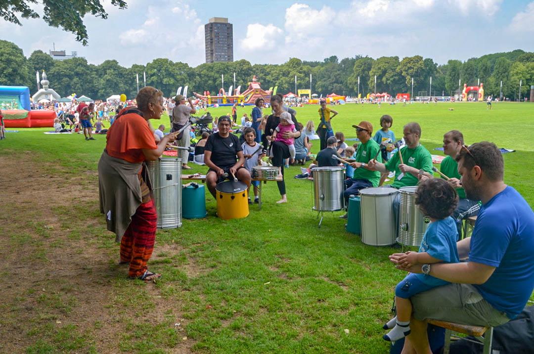 Gruppe von Trommlern unter Anleitung im Kreis auf der Wiese sitzend