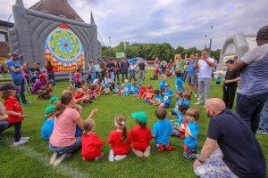 Familien.Spiele.Fest   Kinder sitzen im Kreis und werden zum Spiel angeleitet. Inklusion in allen Bereichen.