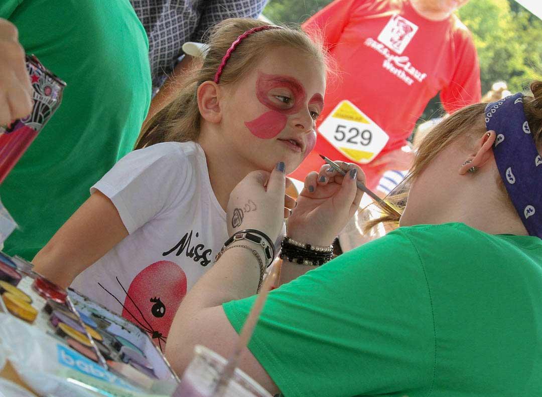 Familien.Spiele.Fest | Ein Mädchen wird geschminkt und lächelt erwartungsvoll. Inklusion in allen Bereichen.