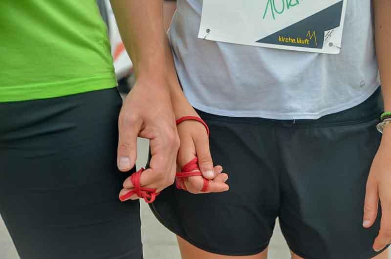 Hände sind mit einem Band verbunden