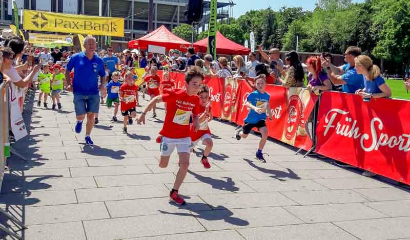 Kinder werden von den Zuschauern beim Laufen angefeuert.