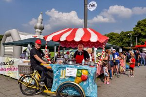 Familien.Spiele.Fest in Köln | Im Vordergrund ein Fahrrad-Eiswagen. Ein Mann sitzt auf dem Fahrrad und schaut freundlich in die Kamera. Eine Frau steht hinter dem Wagen und bietet das Eis an.