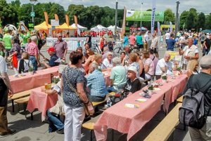 Familien.Spiele.Fest in Köln | Überblick über den Festplatz, Menschen sitzen zusammen, sind im Gespräch, essen, trinken oder machen sich gerade auf den Weg.